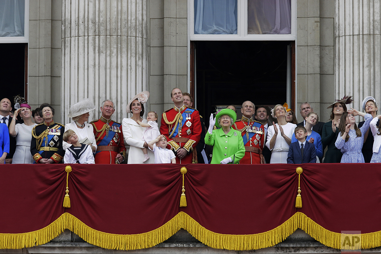 "Britain's Queen Elizabeth II waves as she watches the flypast, with Prince Philip, to right, Prince William, centre, with his son Prince George, front, Kate, Duchess of Cambridge holding Princess Charlotte, centre left, with The Prince of Wales standing with The Duchess of Cornwall, and Princess Anne, fourth left, on the balcony during the Trooping The Colour parade at Buckingham Palace, in London, on June 11, 2016. Hundreds of soldiers in ceremonial dress marched in London in the annual parade to mark the official birthday of Queen Elizabeth II. The Trooping the Colour tradition originates from preparations for battle, when flags were carried or ""trooped"" down the rank for soldiers to see. (AP Photo/Tim Ireland)"