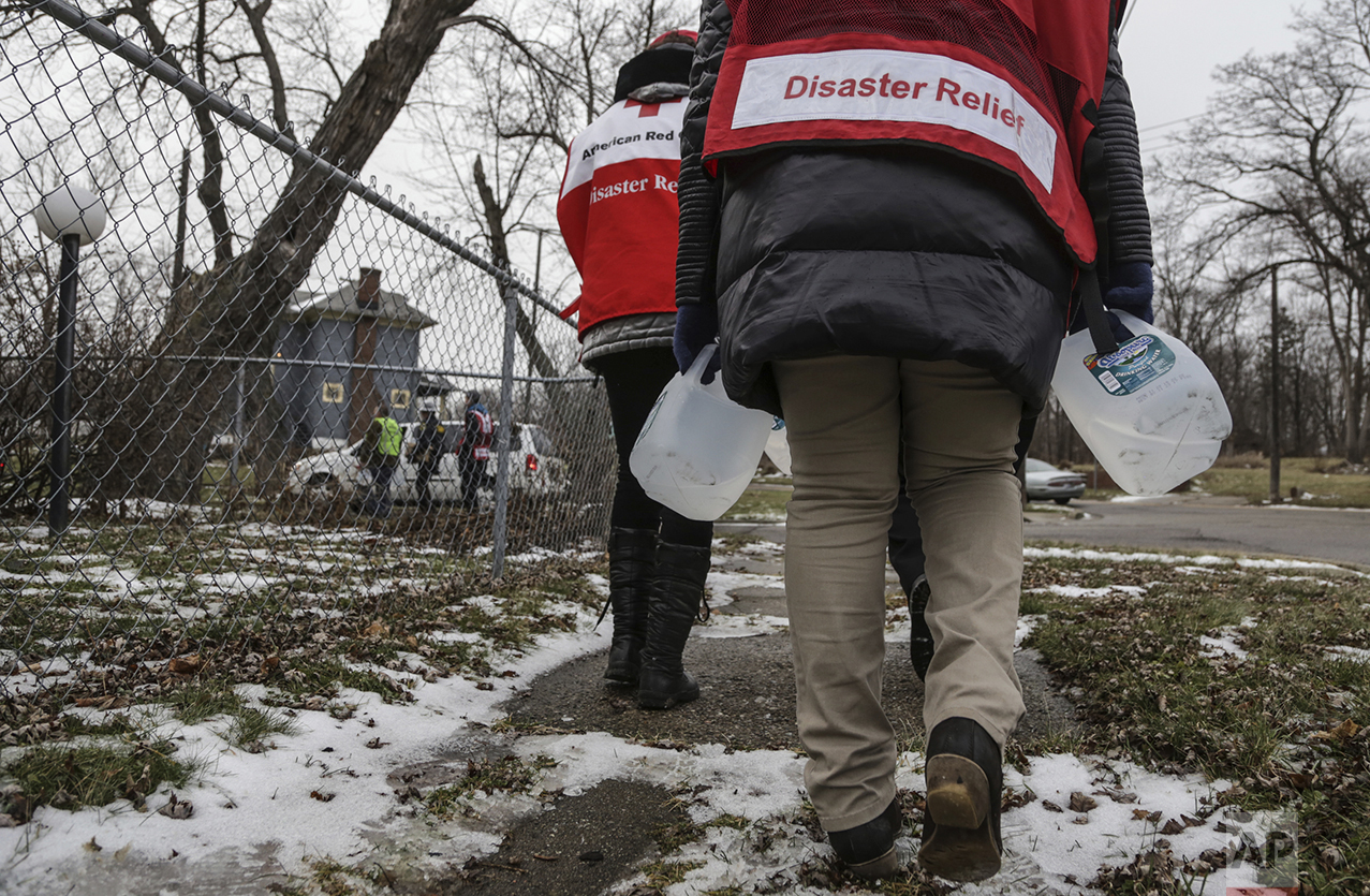 Members of the Red Cross deliver jugs of free purified water and water filters door-to-door to residents dealing with the water crisis on the north side of Flint, Mich., on Jan. 8, 2016. (Ryan Garza/Detroit Free Press via AP)