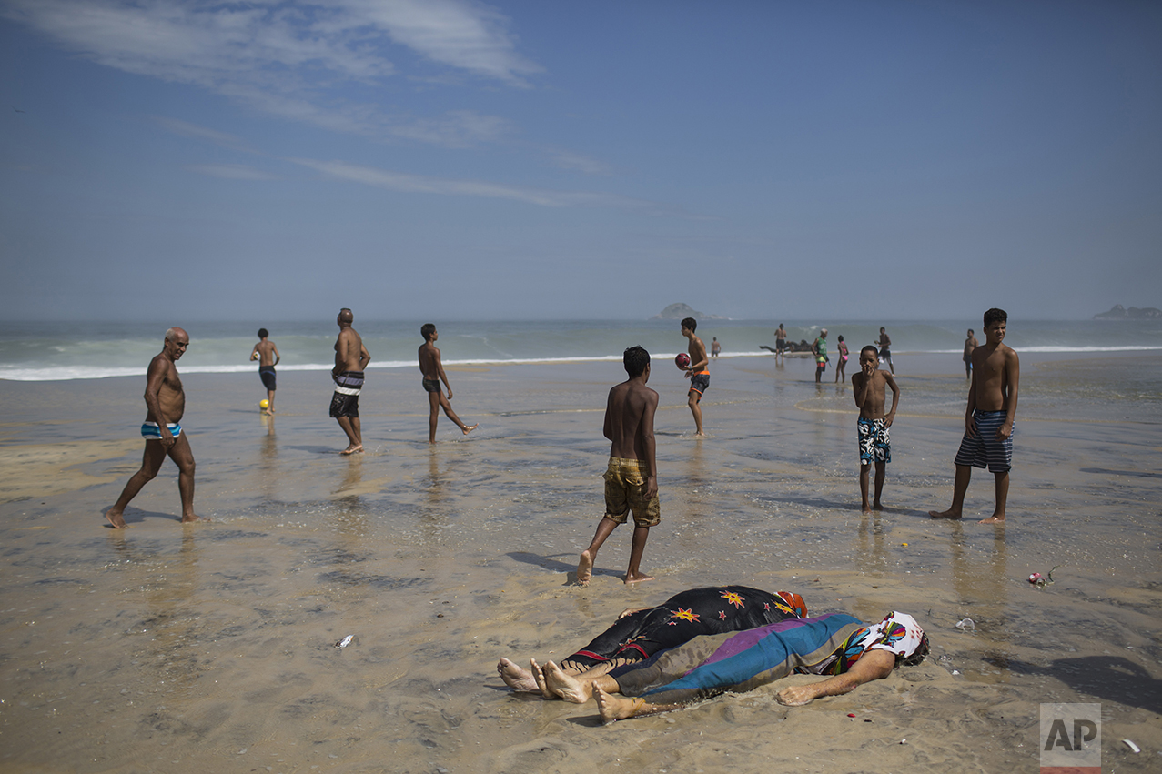 Bodies recovered by rescue workers lie on the sand as sunbathers walk past after a bike lane collapsed in Rio de Janeiro, Brazil, on April 21, 2016. A new elevated bike path that was heralded as a top legacy project of the Rio de Janeiro Olympics collapsed, killing at least two people. (AP Photo/Felipe Dana)