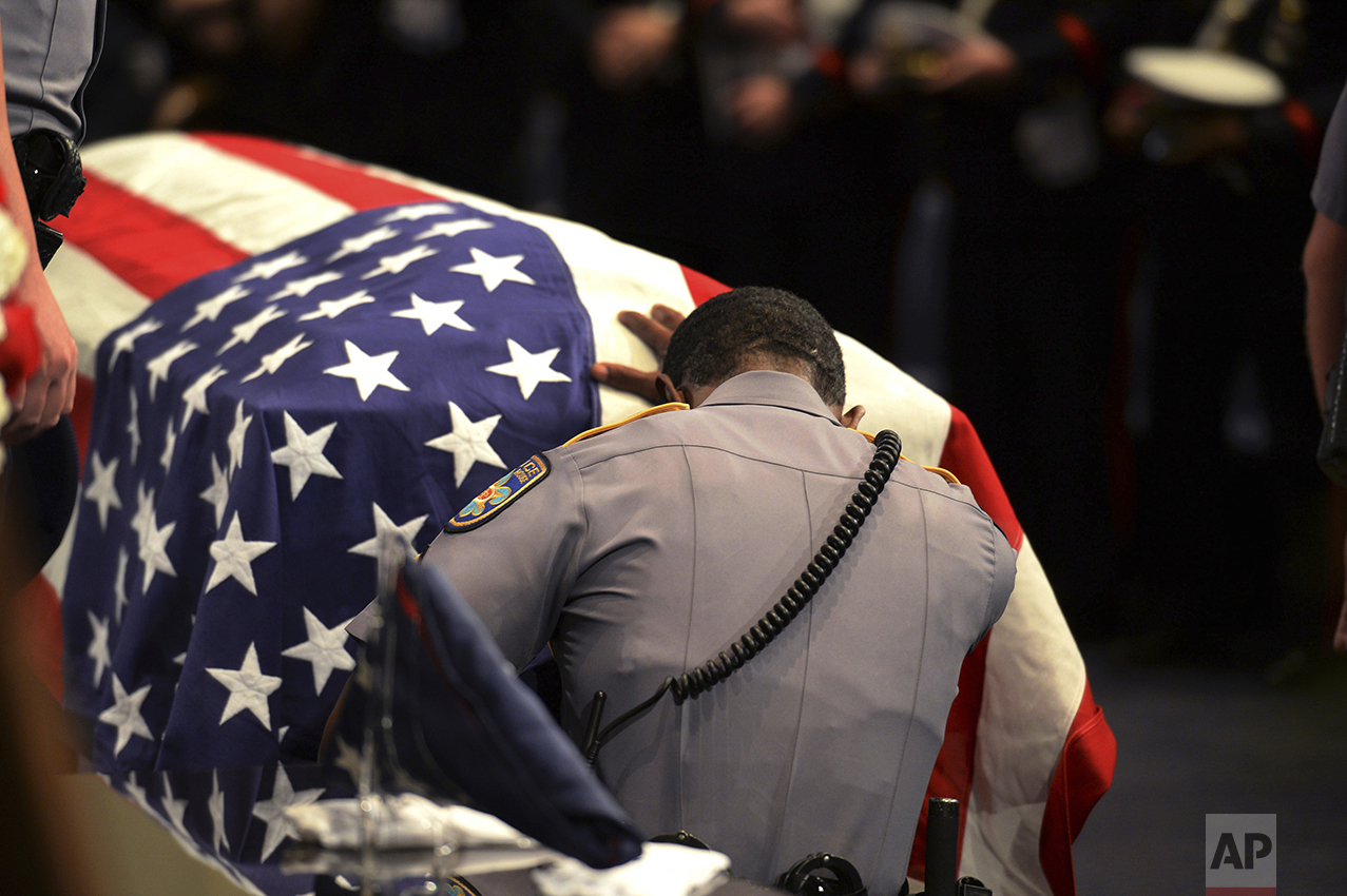 A member of Baton Rouge police Cpl. Montrell Jackson's unit kneels and touches his casket during his funeral service at the Living Faith Christian Center in Baton Rouge, La., on July 25, 2016. Jackson, slain by a gunman who authorities said targeted law enforcement, is the last of the three Louisiana law enforcement officers killed in an ambush to be buried. (Patrick Dennis/Baton Rouge Advocate via AP, Pool)