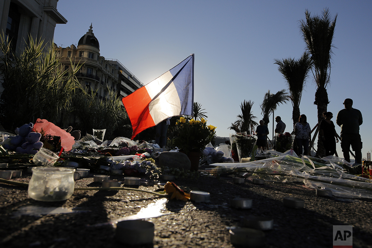 A French flag stands tall within a floral tribute for the victims killed during a deadly attack on the famed Boulevard des Anglais in Nice, southern France, on July 17, 2016. (AP Photo/Laurent Cipriani)