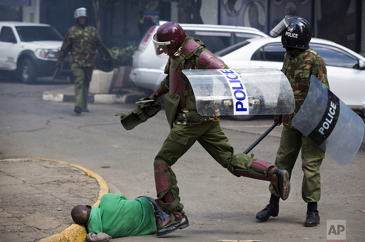 A Kenyan riot policeman repeatedly kicks a protester who lies in the street after tripping over while trying to flee from them, during a protest in downtown Nairobi, Kenya, on May 16, 2016. Kenyan police tear-gassed and beat opposition supporters during a protest demanding the disbandment of the electoral authority over alleged bias and corruption. (AP Photo/Ben Curtis)