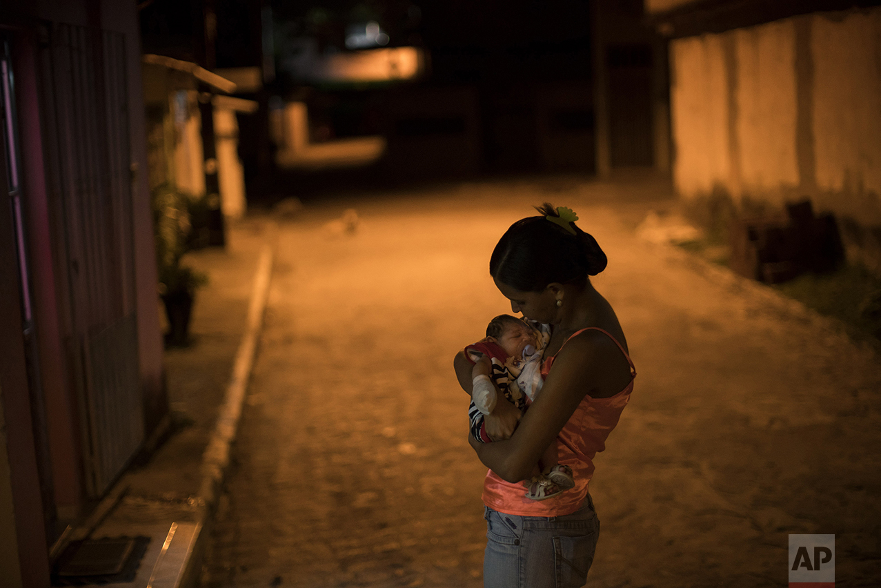 Daniele Ferreira dos Santos holds her son, Juan Pedro, who was born with microcephaly, outside her house in Recife, Pernambuco state, Brazil, on Jan. 26, 2016. Santos was never diagnosed with Zika, but she blames the virus for her son's defect and for the terrible toll it has taken on her life. (AP Photo/Felipe Dana)
