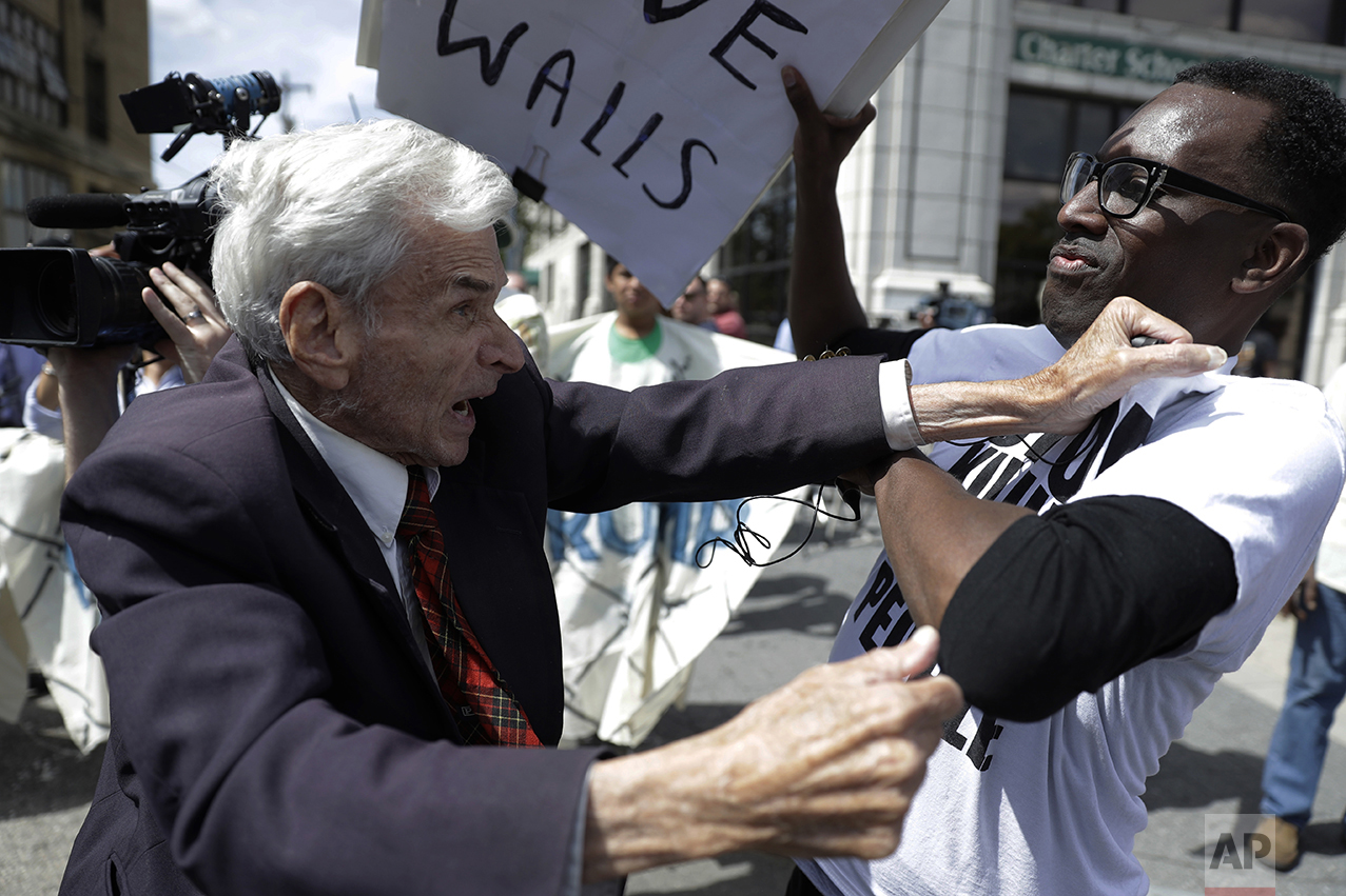 Jerry Lambert, left, a supporter of Republican presidential candidate Donald Trump, and Asa Khalif with Black Lives Matter scuffle after Khalif took Lambert's sign outside the location where Trump is to meet with African American business and civic leaders in Philadelphia on Sept. 2, 2016. (AP Photo/Matt Rourke)