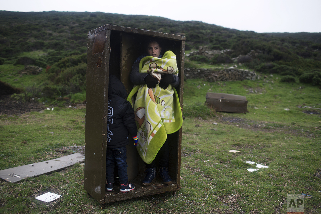 A Syrian woman takes shelter with her children in an iron box during a rainfall after they arrived from Turkey to the Greek deserted island of Pasas near Chios, on Jan. 20, 2016. Thousands of migrants and refugees continue to reach Greece's shores despite the winter weather. (AP Photo/Petros Giannakouris)