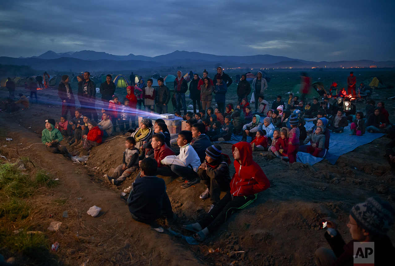 Children watch an animated movie in a field at the northern Greek border station of Idomeni on March 5, 2016. The Idomeni border crossing in the Greek region of Central Macedonia has become a bottleneck, where thousands of migrants are trapped as they try to find refuge and a better life in Europe. (AP Photo/Vadim Ghirda)