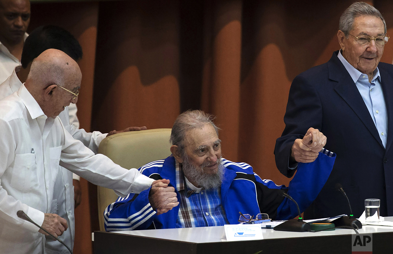 Fidel Castro sits as he clasps hands with his brother, Cuban President Raul Castro, right, and second secretary of the Central Committee, Jose Ramon Machado Ventura, moments before the playing of the Communist party hymn during the closing ceremonies of the 7th Congress of the Cuban Communist Party, in Havana, Cuba, on April 19, 2016. (Ismael Francisco/Cubadebate via AP)