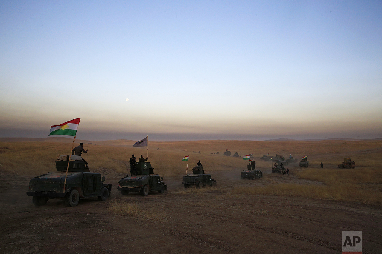 A Peshmerga convoy drives toward the frontline in Khazer, about 30 kilometers (19 miles) east of Mosul, Iraq, on Oct. 17, 2016. The Iraqi military and the country's Kurdish forces have launched operations to the south and east of militant-held Mosul. (AP Photo/Bram Janssen)