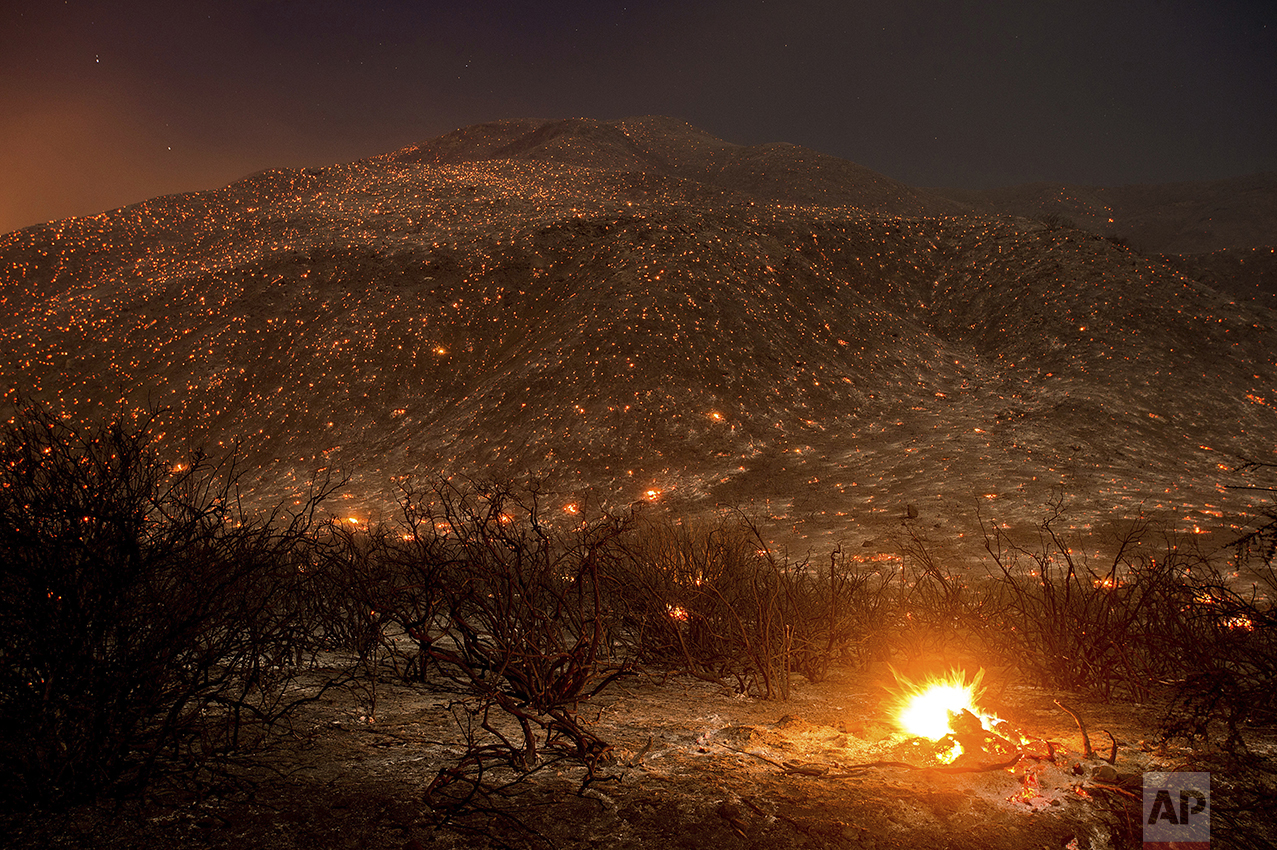 Embers from a wildfire smolder along Lytle Creek Road near Keenbrook, Calif., on Aug. 17, 2016. (AP Photo/Noah Berger)
