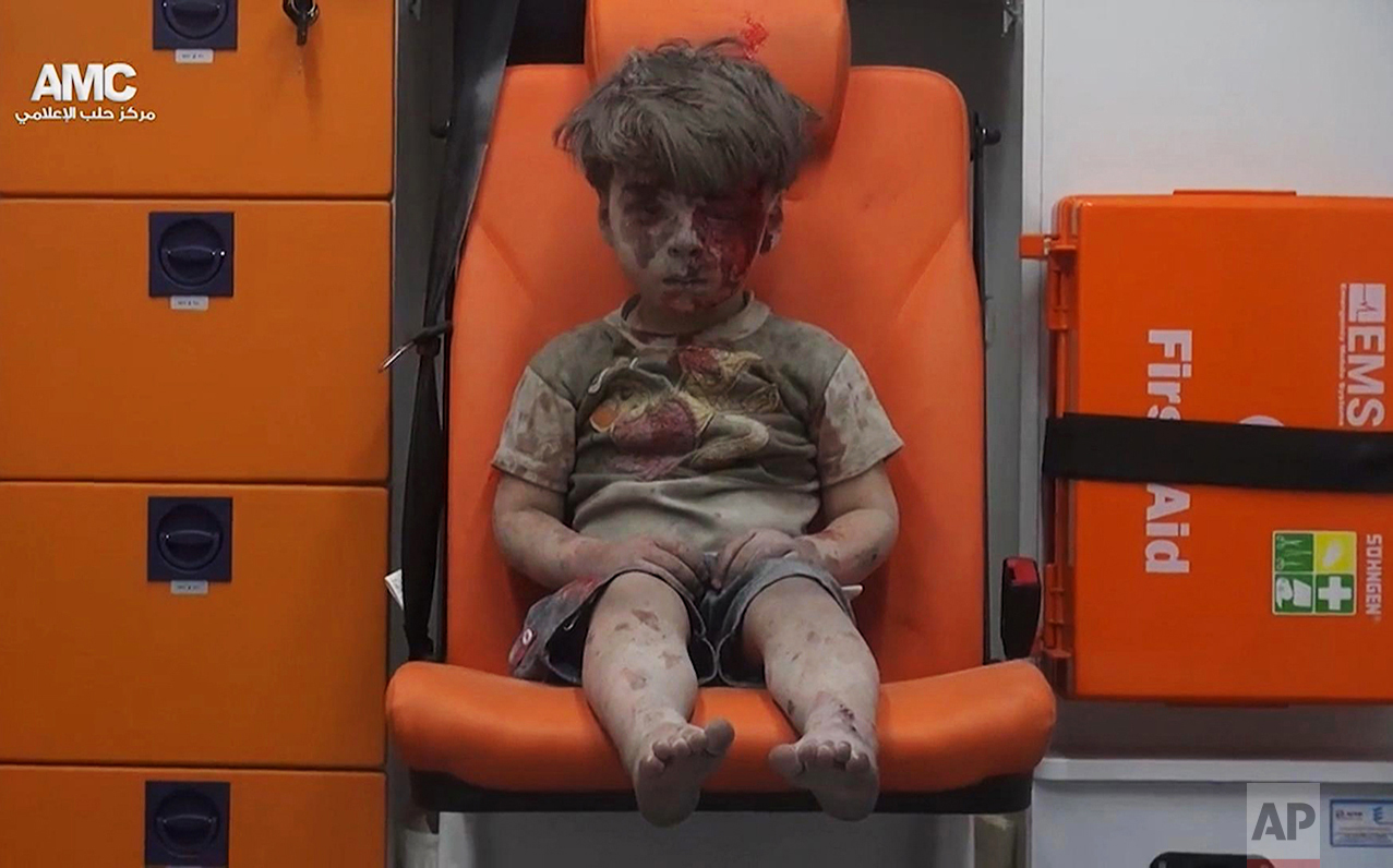 In this frame grab taken from video provided by the Syrian anti-government activist group Aleppo Media Center (AMC), 5-year-old Omran Daqneesh sits in an ambulance after being pulled out of a building hit by an airstrike in Aleppo, Syria, on Aug. 17, 2016. The White Helmets were among the crowd of first responders who pulled Daqneesh and his family from the rubble of their apartment building. (Aleppo Media Center via AP)