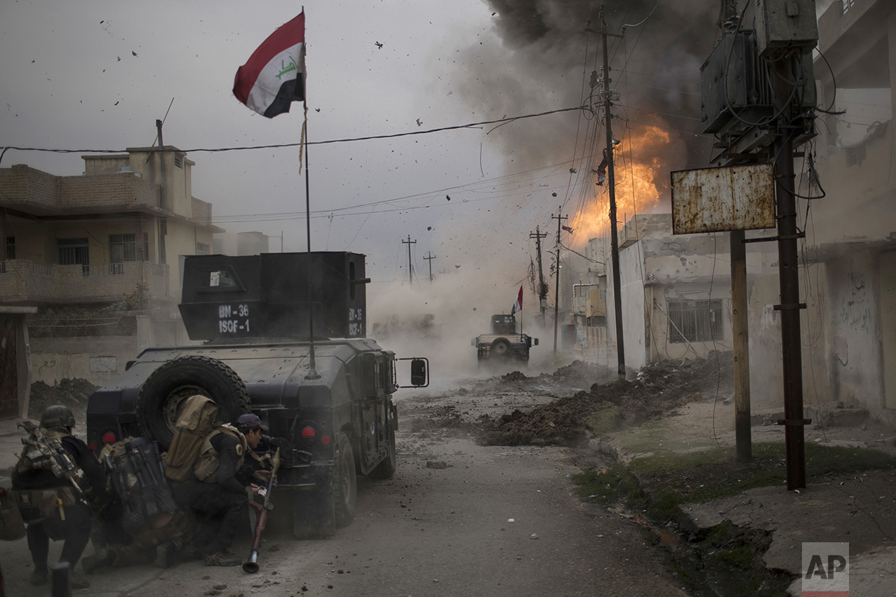A car bomb explodes next to Iraqi special forces armored vehicles as they advance toward territory held by the Islamic State group in Mosul, Iraq, on Nov. 16, 2016. (AP Photo/Felipe Dana)