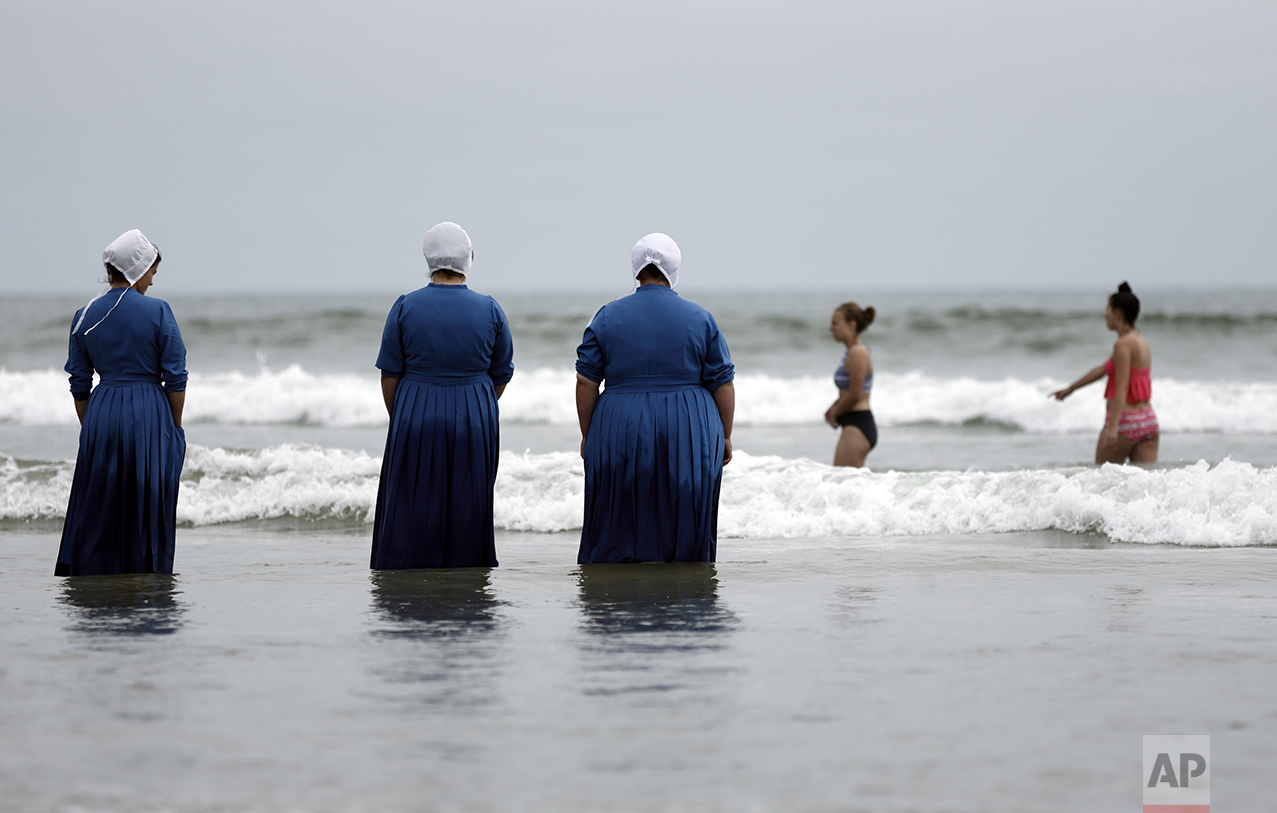 Rosa Graber, third from left, Margerie Steury, second left, and Joanne Steury, left, look out to sea as they touch Pacific Ocean waters for the first time during a family trip from their Amish community in Michigan, on June 9, 2016, in Coronado, Calif. (AP Photo/Gregory Bull)