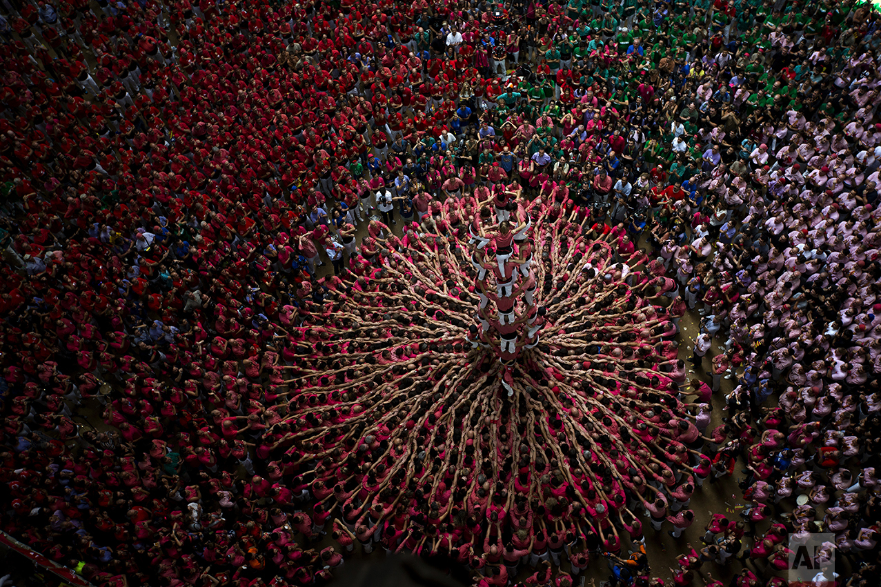 """Members of """"Vella de Xiquets de Valls"""" try to complete their human tower during the 26th Human Tower Competition in Tarragona, Spain, on Oct. 2, 2016. The tradition of building human towers, or Castells, dates back to the 18th century and takes place during festivals in Catalonia, where """"colles,"""" or teams, compete to build the tallest and most complicated towers. The structure of the castells varies depending on their complexity. A castell is considered completely successful when it is loaded and unloaded without falling apart. The highest castell in history was a 10 floor structure with 3 people in each floor. In 2010 castells were declared by UNESCO one of the Masterpieces of the Oral and Intangible Heritage of Humanity. (AP Photo/Emilio Morenatti)"""