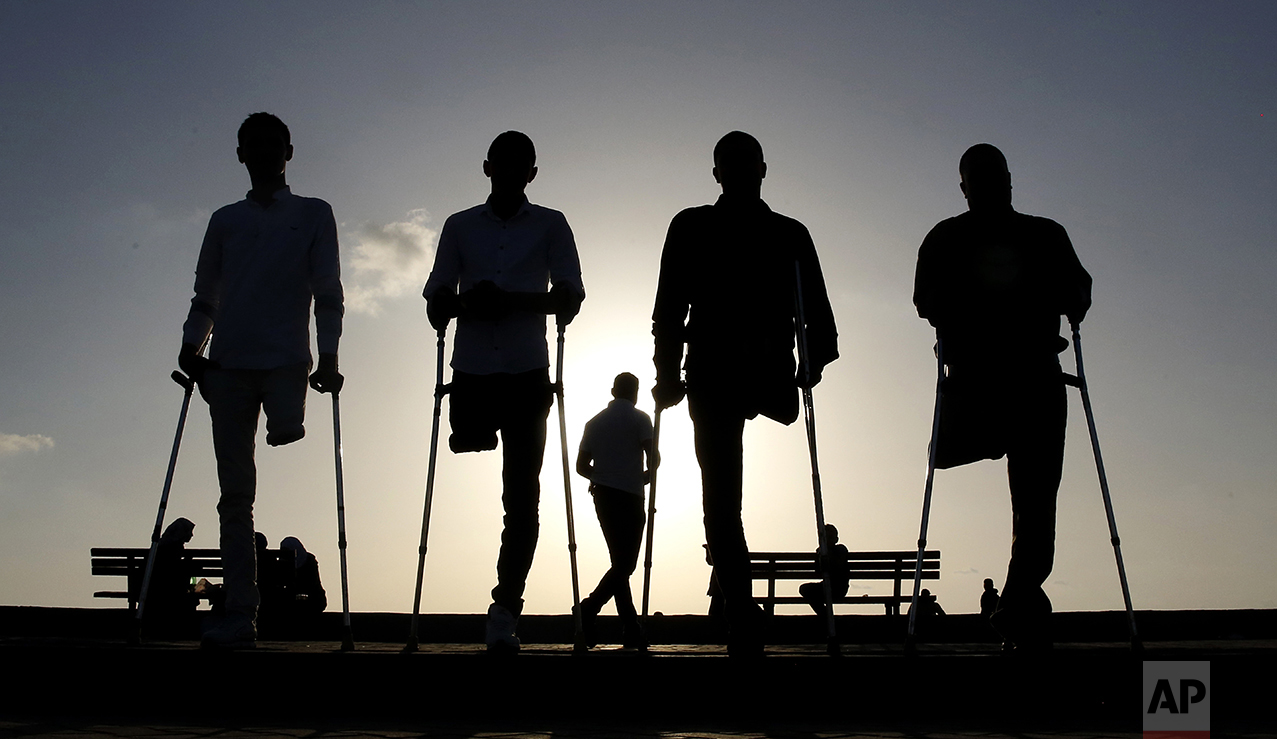 Four Palestinian friends who were injured during conflicts walk by the sea at Gaza's small fishing harbor on Oct. 24, 2016. Fighting has left thousands of people with disabilities or no limbs in this Palestinian enclave. (AP Photo/Hatem Moussa)