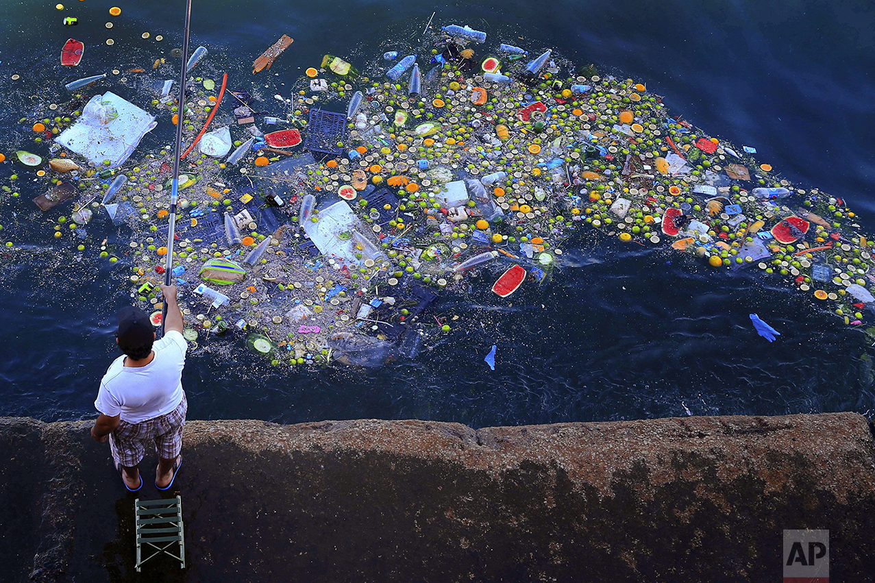 A man holds a fishing rod as floating trash hits the coastline of the Mediterranean Sea in Beirut, Lebanon, on Sept. 29, 2016. (AP Photo/Hassan Ammar)