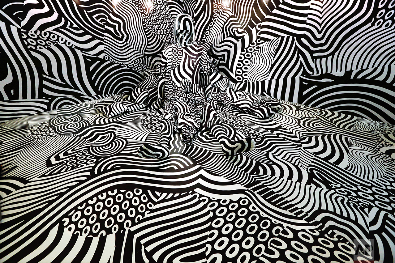 """A model named feebee poses as part of art installation """"Narcissism : Dazzle room"""" made by artist Shigeki Matsuyama at rooms33 fashion and design exhibition in Tokyo on Sept. 14, 2016. Matsuyama's installation featured a strong contrast of black and white, which he learned from dazzle camouflage used mainly in World War I. (AP Photo/Eugene Hoshiko)"""