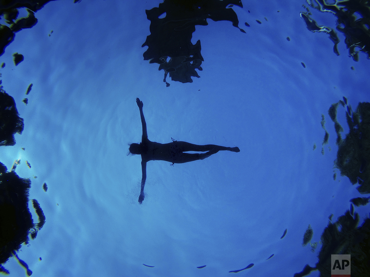 In this underwater picture a woman floats in a swimming pool during a summer day in Madrid, Spain, Aug. 28, 2016. (AP Photo/Daniel Ochoa de Olza)