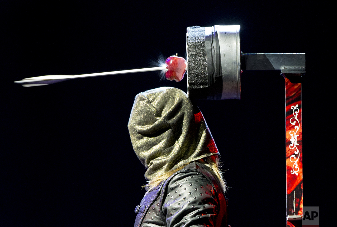 Ben Blaque, a crossbow sharpshooter, stands still after firing a crossbow wearing a hood, that then triggered a series of pre-set crossbows culminating in an arrow piercing the apple above his head, during media event to promote the magic show, The Illusionists 1903, at the National Auditorium in Mexico City, on July 13, 2016. (AP Photo/Rebecca Blackwell)