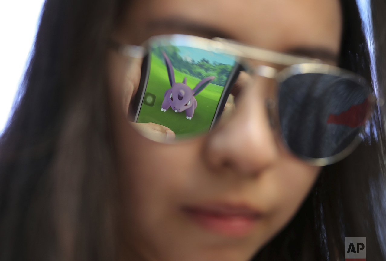 """A mobile screen is reflected on a fan's sunglasses as she plays """"Pokemon Go"""" in Hong Kong on July 25, 2016. Pokemon fans participated in creature hunting as the app was released to both iPhone and Android users. (AP Photo/Kin Cheung)"""