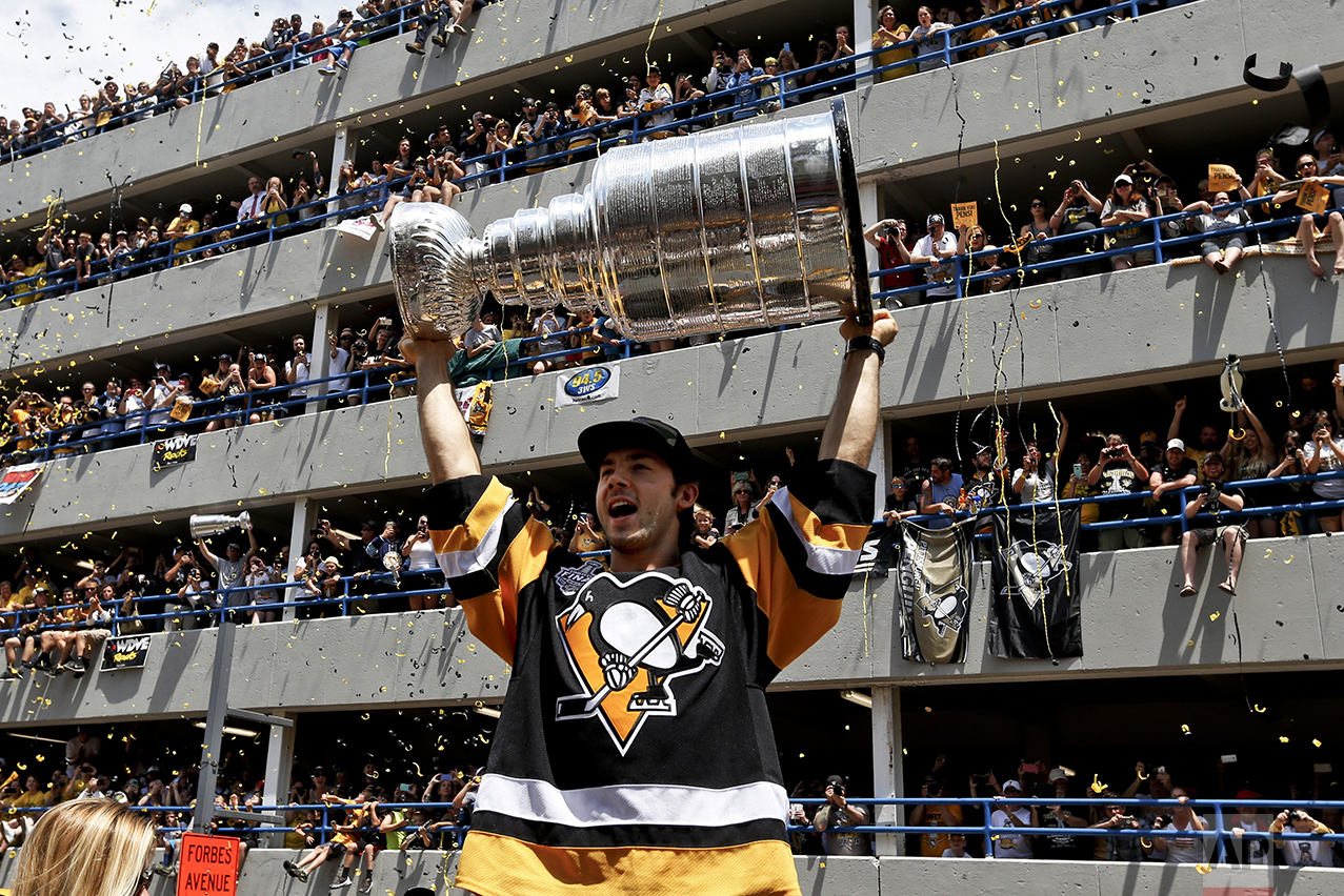 Pittsburgh Penguins' Kris Letang holds the Stanley Cup overhead in front of some of the crowd packing a parking lot along the victory parade route in Pittsburgh, Pa., on June 15, 2016. The Penguins defeated the San Jose Sharks to win the NHL hockey championship. (AP Photo/Keith Srakocic)
