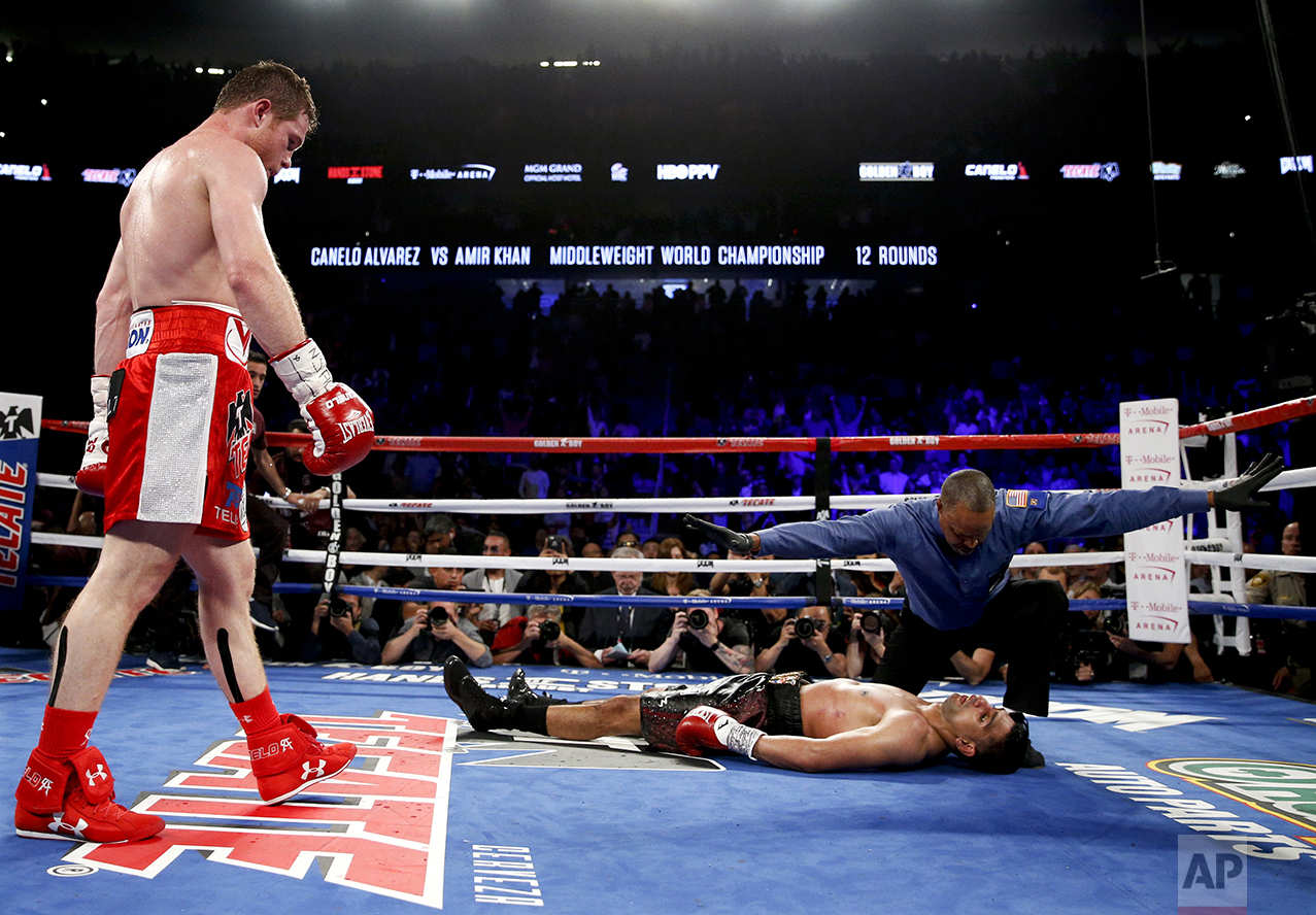 Canelo Alvarez, left, watches after knocking down Amir Khan during their WBC middleweight title fight on May 7, 2016, in Las Vegas. (AP Photo/John Locher)