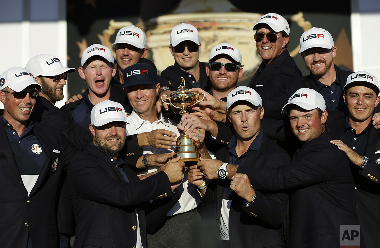 United States captain Davis Love III is surrounded by his players as they pose for a picture during the closing ceremony of the Ryder Cup golf tournament on Oct. 2, 2016, at Hazeltine National Golf Club in Chaska, Minn. (AP Photo/David J. Phillip)