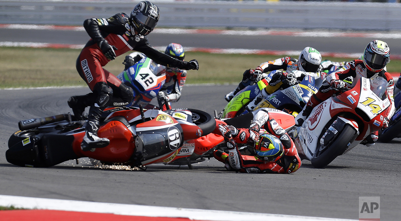 Axel Pons, left, and Xavier Simeon, center on the ground, crash on the opening lap of the San Marino Moto2 grand prix at the Misano circuit, in Misano Adriatico, Italy, on Sept. 11, 2016. (AP Photo/Antonio Calanni)