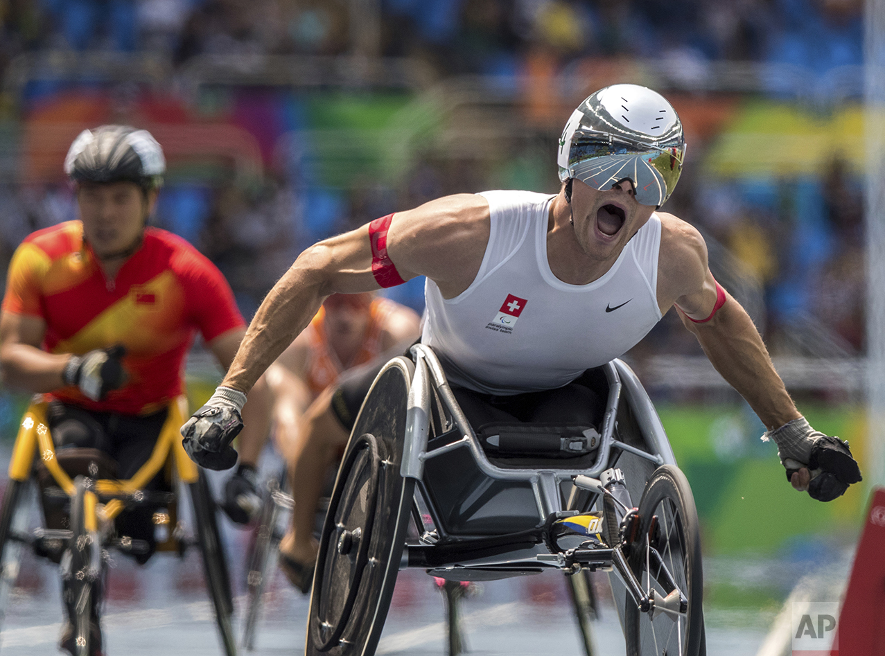 In this photo released by the IOC, wheelchair racer Marcel Hug, of Switzerland, celebrates winning the athletics men's final 800-meter T54 athletics event at Olympic Stadium during the Paralympic Games in Rio de Janeiro, Brazil, on Sept. 15, 2016. (Simon Bruty/OIS, IOC via AP)
