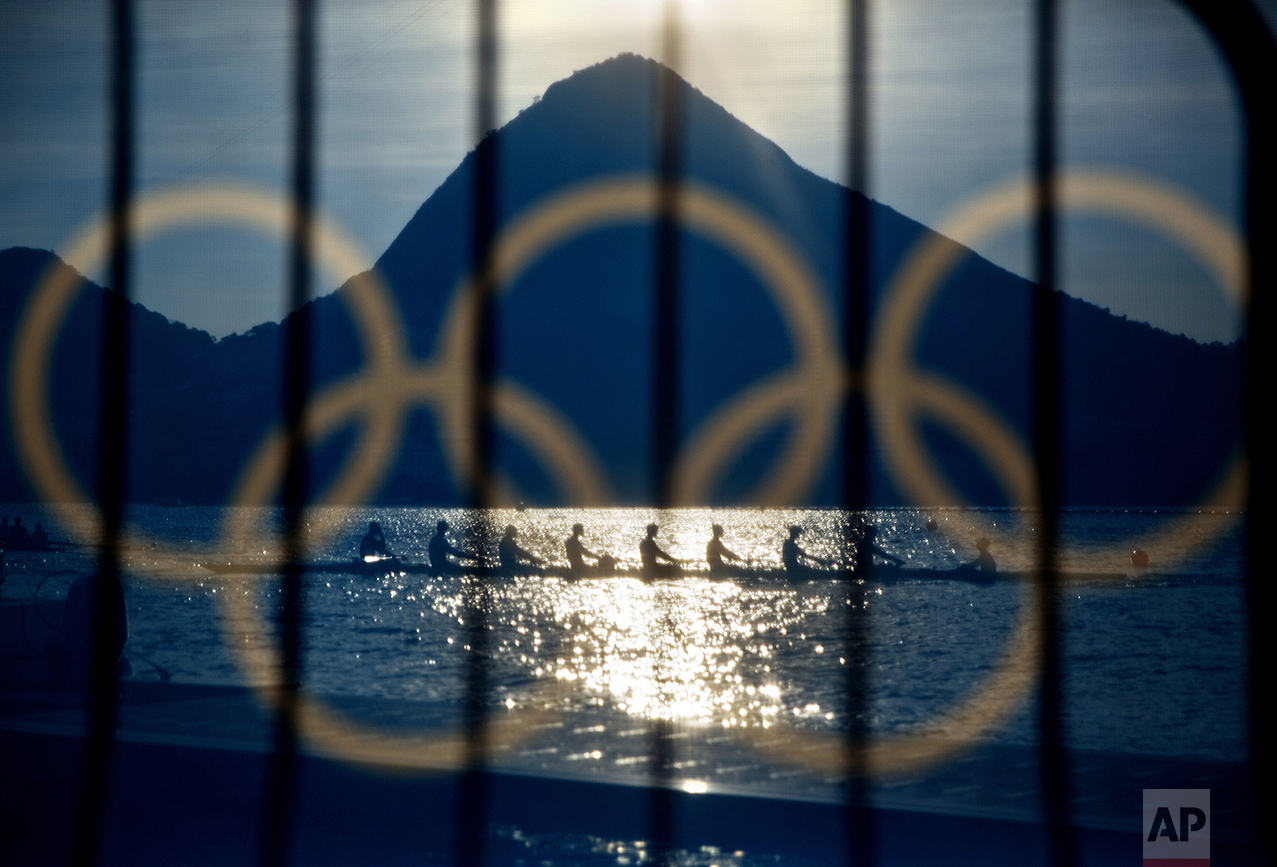 Rowers are seen through a screen decorated with the Olympic rings as they practice at the rowing venue in Lagoa at the 2016 Summer Olympics in Rio de Janeiro, Brazil, on Aug. 7, 2016. (AP Photo/David Goldman)