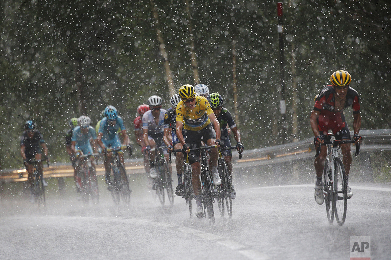 Australia's Richie Porte, right, breaks away from the group with Britain's Chris Froome, wearing the overall leader's yellow jersey, as they climb towards Andorra Arcalis in pouring rain and hail during the ninth stage of the Tour de France cycling race over 184.5 kilometers (114.3 miles) with start in Vielha Val d'Aran, Spain, and finish in Andorra Arcalis, Andorra, on July 10, 2016. (AP Photo/Christophe Ena)