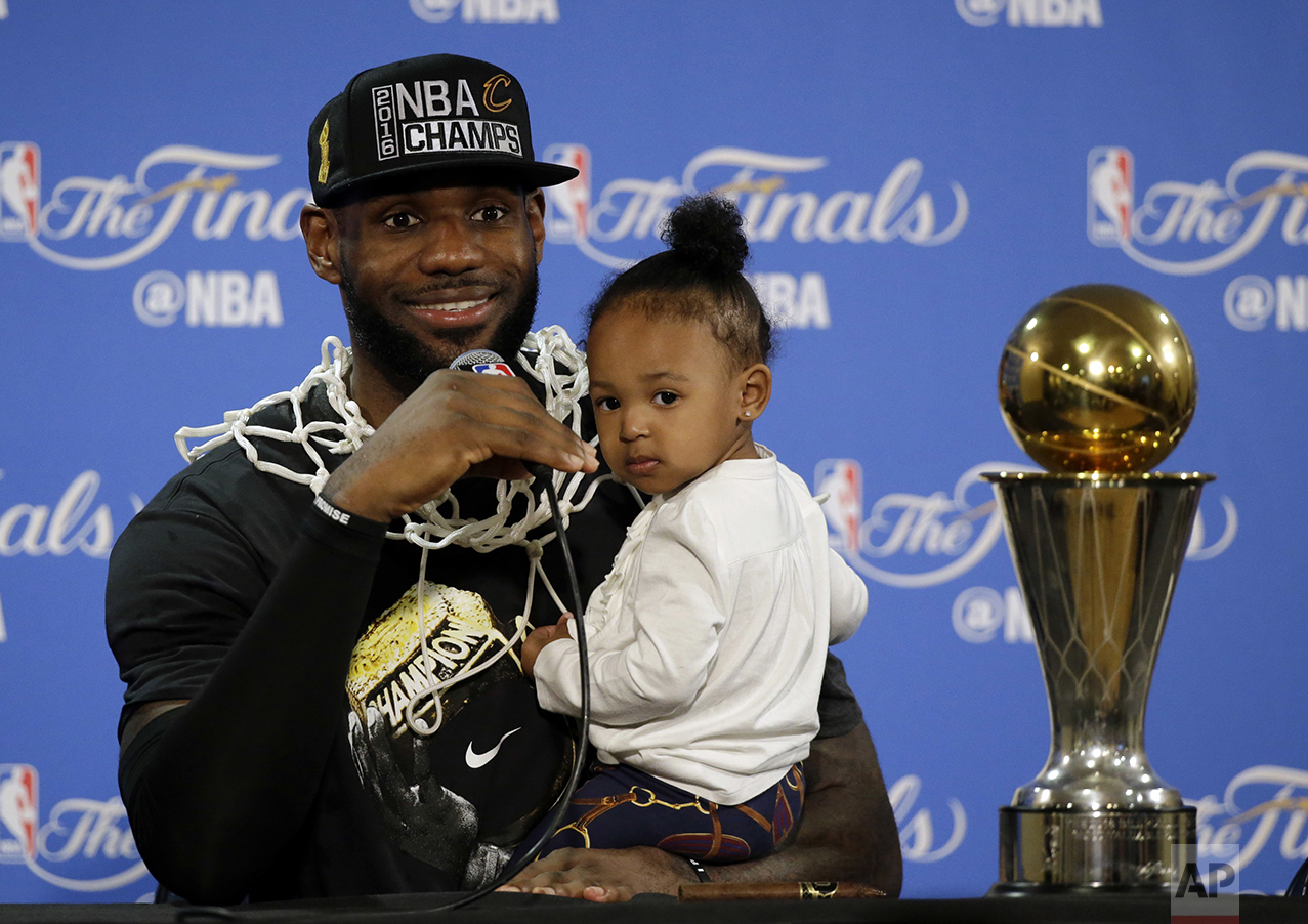 Cleveland Cavaliers' LeBron James answers questions as he holds his daughter Zhuri, during a post-game press conference following Game 7 of basketball's NBA Finals on June 19, 2016, in Oakland, Calif. Cleveland won 93-89. (AP Photo/Eric Risberg)