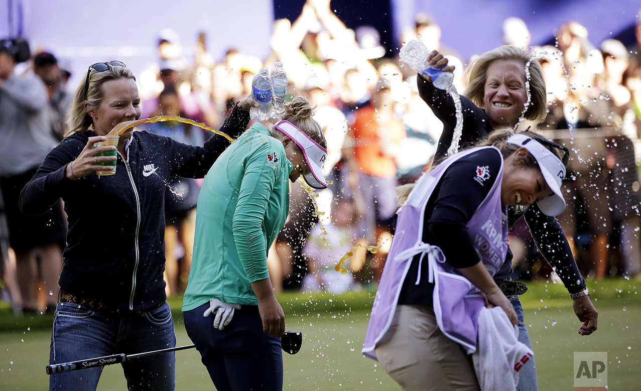 Brooke Henderson, of Canada, second left, and her caddy and sister Brittany Henderson are doused with water and sports drinks on the 18th green after Brooke Henderson won the Women's PGA Championship golf tournament at Sahalee Country Club on June 12, 2016, in Sammamish, Wash. (AP Photo/Elaine Thompson)