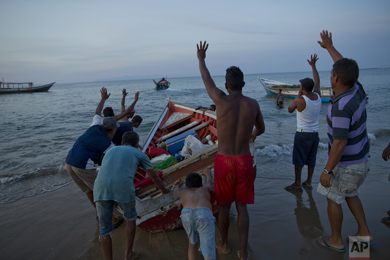 In this Nov. 2, 2016 photo, fishermen from the Marval family give instructions to a skiff towing their boat to sea as they head out for a night of fishing in Punta de Araya, Sucre state, Venezuela. Every night, the fishermen risk getting robbed and even killed by pirates roaming the seas. (AP Photo/Rodrigo Abd)