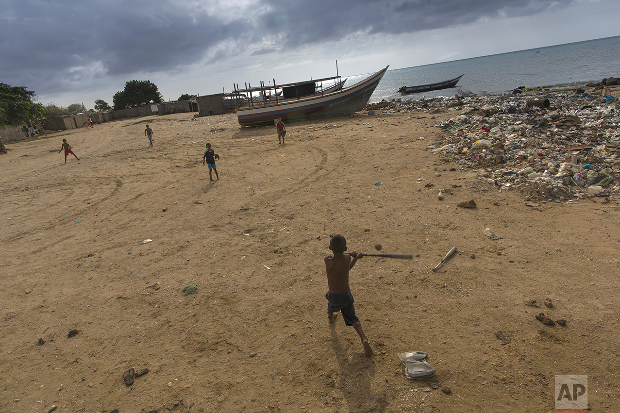 In this Nov. 8, 2016 photo, children play baseball on the beach in Punta de Araya, Sucre state, Venezuela. Many private fishing companies have left Venezuela for other countries because the government requires them to sell half of their catch for virtually worthless bolivars. (AP Photo/Rodrigo Abd)