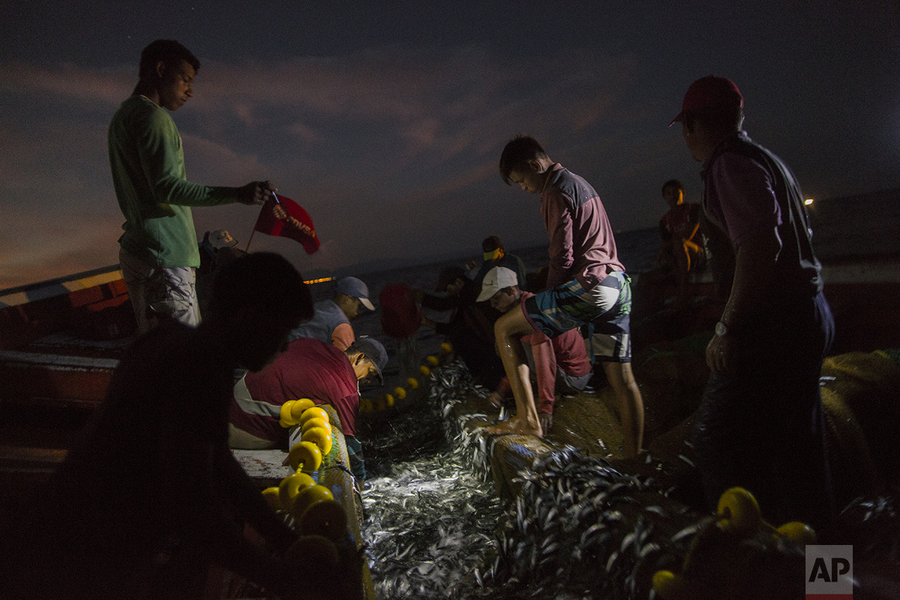 """In this Oct. 31, 2016 photo, the Marval family fish at night in the sea, off Punta de Araya, Sucre state, Venezuela. Sucre was the epicenter of food riots that swept through the country in June, and Punta de Araya families got through the summer by eating """"dog soup,"""" a broth made from seawater and the small fish that are usually thrown back. (AP Photo/Rodrigo Abd)"""