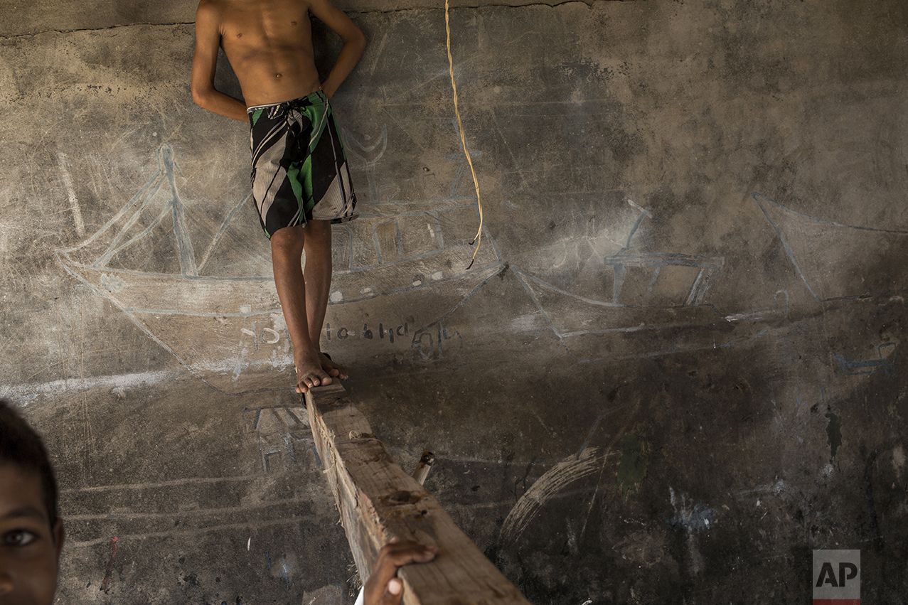In this Oct. 30, 2016 photo, children play inside a depot used by fishermen to store their nets and repair boats in Punta de Araya, Sucre state, Venezuela. Desperate, Venezuelans are stealing what remains from fatter times, robbing fishing boats of their nets, power generators and outboard motors, making the warm Caribbean sea increasingly a grim free-for-all. (AP Photo/Rodrigo Abd)
