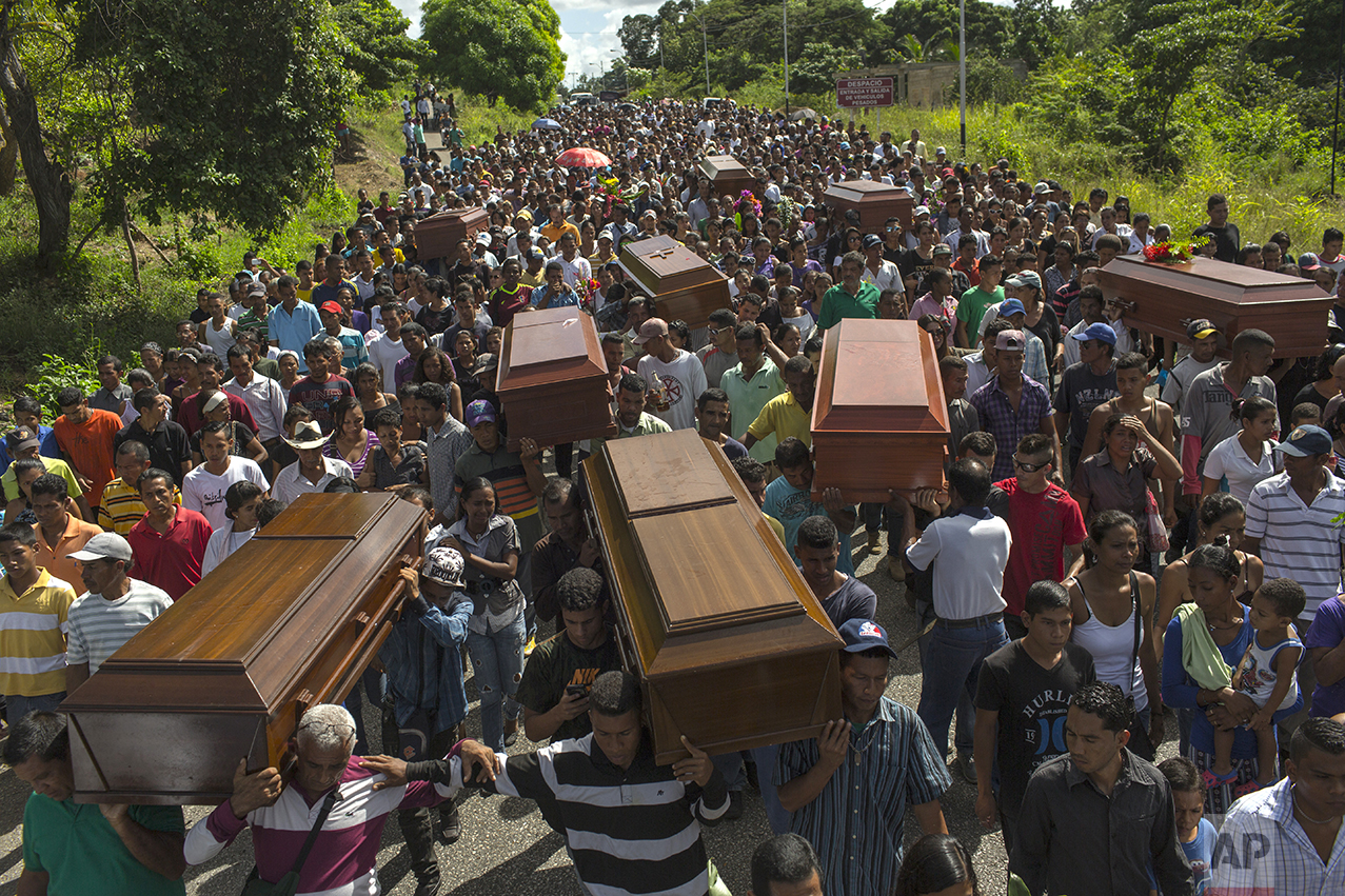In this Nov. 13, 2016 photo, villagers carry the remains of nine slain men from a fishing family to the cemetery in Cariaco, Sucre state, Venezuela. Five law enforcement officers were charged with storming the village and killing these men, who were widely thought to have belonged to a gang. (AP Photo/Rodrigo Abd)
