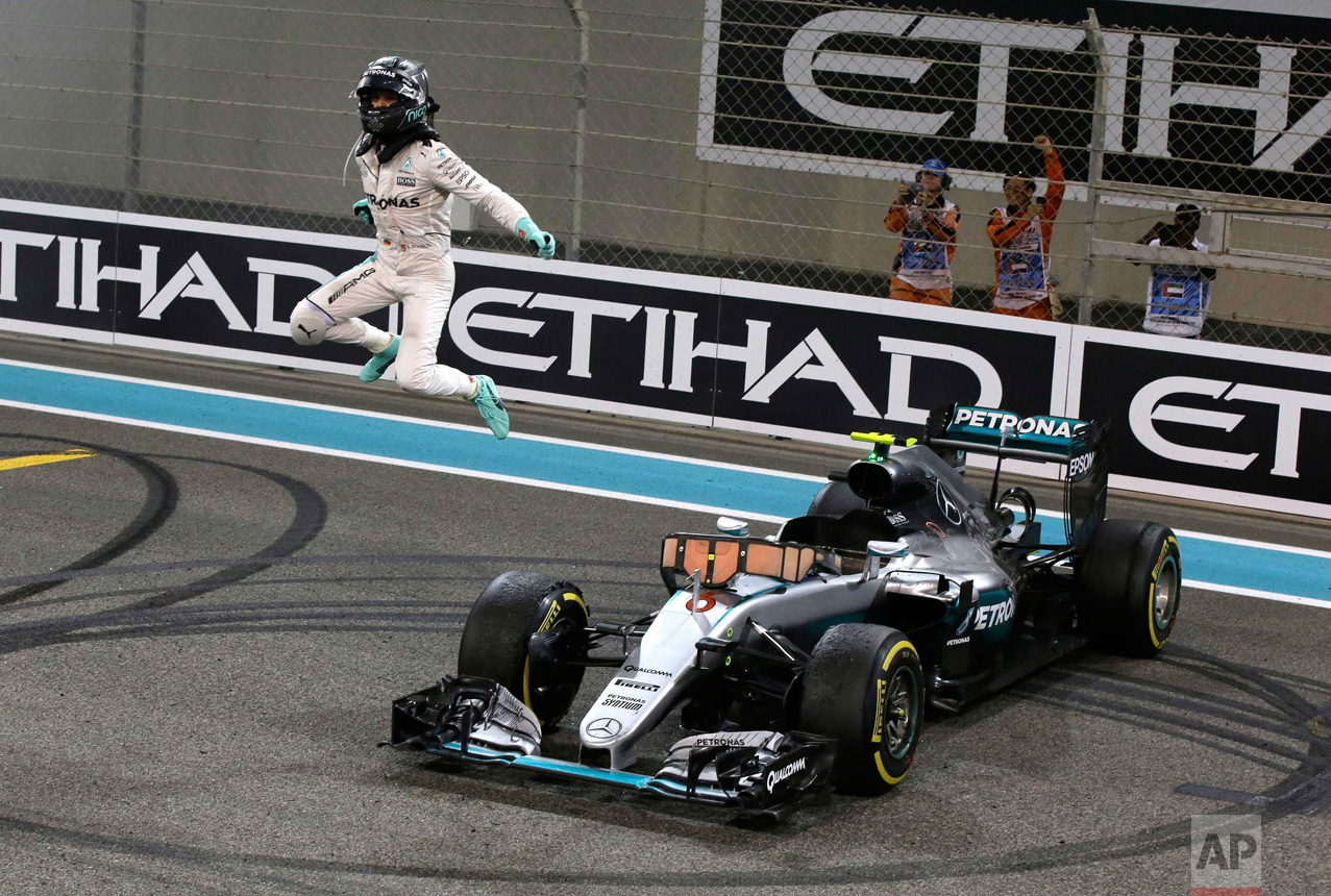 In this Sunday, Nov. 27, 2016 photo, Mercedes F1 driver Nico Rosberg of Germany celebrates after finishing second to win the 2016 world championship during the Emirates Formula One Grand Prix at the Yas Marina racetrack in Abu Dhabi, United Arab Emirates. (AP Photo/Luca Bruno)