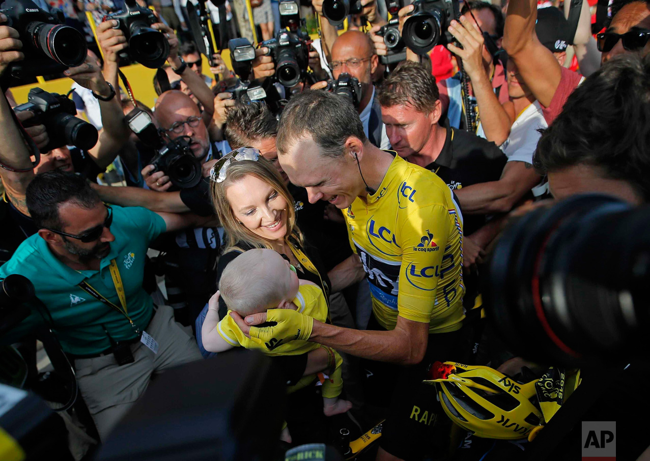 In this Sunday, July 24, 2016 photo, Tour de France champion, Britain's Chris Froome, wearing the overall leaders yellow jersey, is congratulated by his wife Michelle, who holds their baby boy, after the twenty-first stage of the Tour de France cycling race over 113 kilometers (70.2 miles) with start in Chantilly and finish in Paris, France. (AP Photo/Christophe Ena)