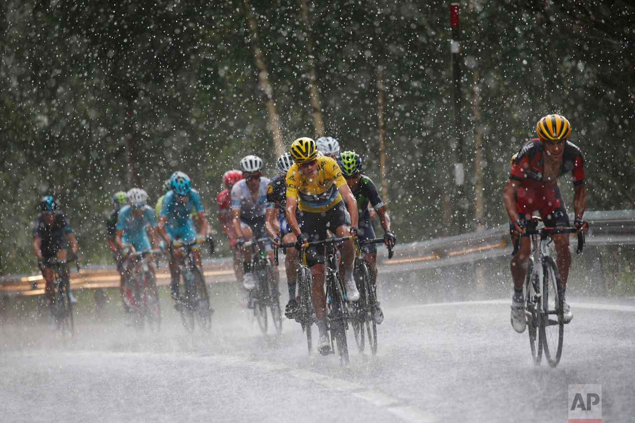In this Sunday, July 10, 2016 photo, Australia's Richie Porte, right, breaks away from the group with Britain's Chris Froome, wearing the overall leader's yellow jersey, as they climb towards Andorra Arcalis in pouring rain and hail during the ninth stage of the Tour de France cycling race over 184.5 kilometers (114.3 miles) with start in Vielha Val d'Aran, Spain, and finish in Andorra Arcalis, Andorra. (AP Photo/Christophe Ena)