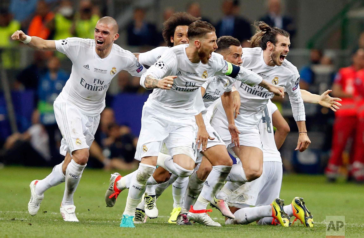 In this Saturday, May 28, 2016 photo, Real Madrid players celebrate after Cristiano Ronaldo scored the winning penalty in a shootout during the Champions League final soccer match between Real Madrid and Atletico Madrid at the San Siro stadium in Milan, Italy. (AP Photo/Antonio Calanni)