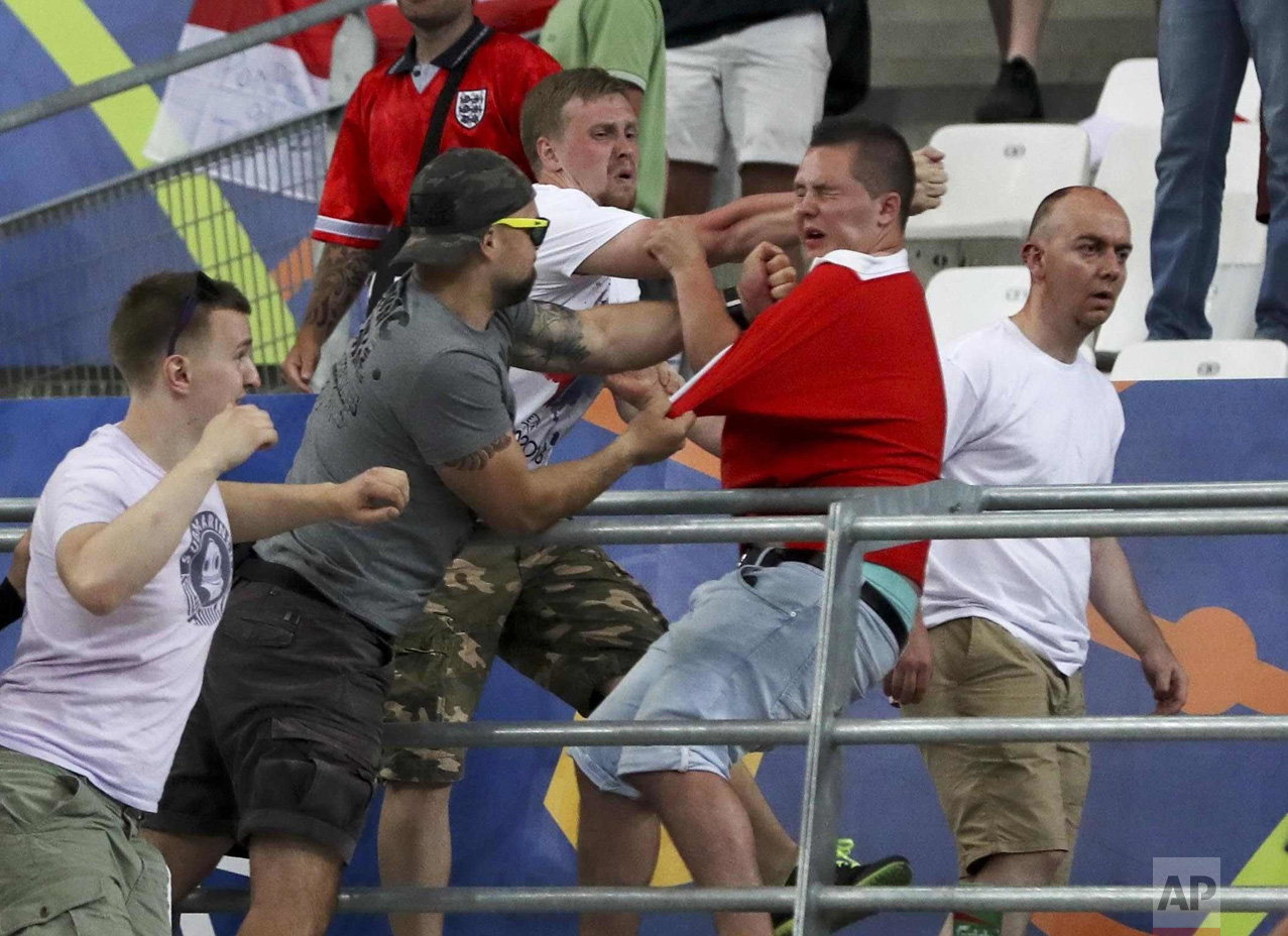 In this Saturday, June 11, 2016 photo, Russian supporters attack an England fan in the stands after the Euro 2016 Group B soccer match between England and Russia, at the Velodrome stadium in Marseille, France. (AP Photo/Thanassis Stavrakis)