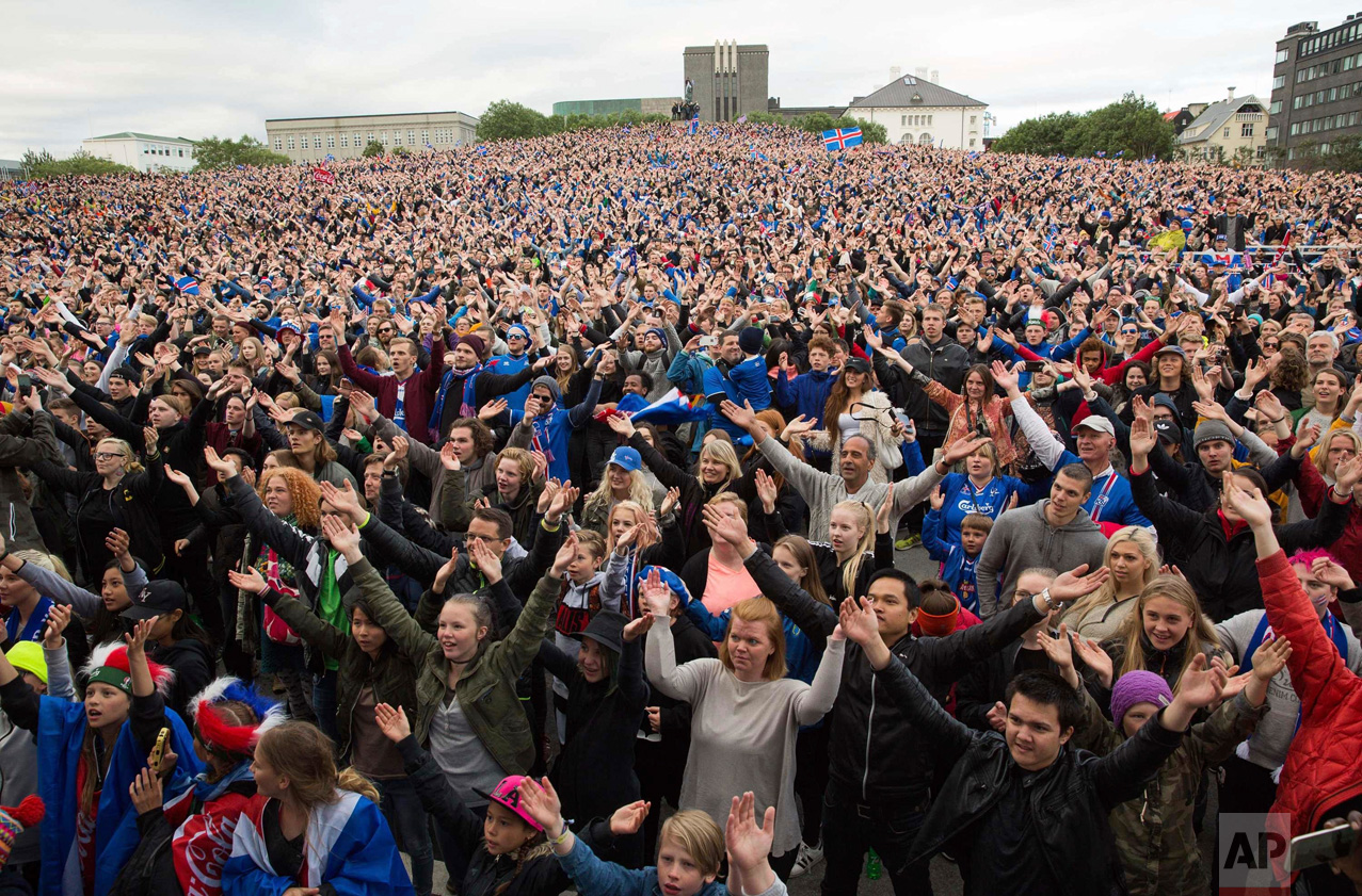 In this Monday June 27, 2016 photo, Icelandic soccer fans celebrate as they watch the Euro 2016 round of 16 match between Iceland and England shown on a screen in Reykjavik, Iceland. Iceland pulled off the shock of the European Championship by beating England 2-1 in the round of 16 on Monday, continuing the improbable run of the smallest nation at the tournament. (AP Photo/Brynjar Gunnarsson)