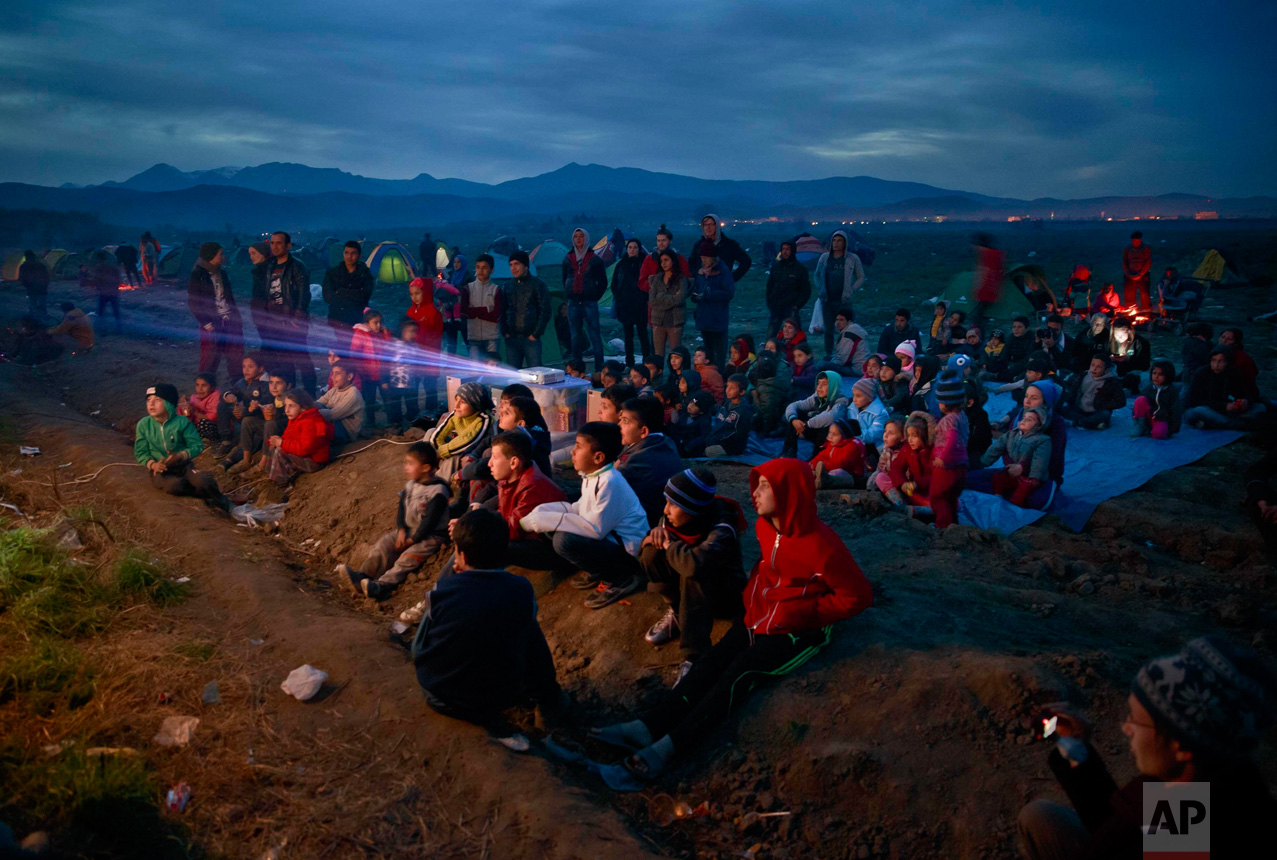 In this March 5, 2016 photo, children watch an animated movie in a field at the northern Greek border station of Idomeni. The Idomeni border crossing in the Greek region of Central Macedonia has become a bottleneck, where thousands of migrants are trapped as they try to find refuge and a better life in Europe. (AP Photo/Vadim Ghirda)