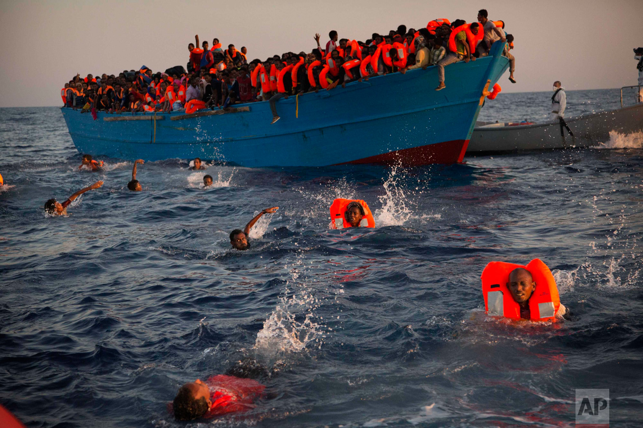 In this Monday, Aug. 29, 2016 photo, migrants, most of them from Eritrea, jump into the water from a crowded wooden boat as they are helped by members of an NGO during a rescue operation at the Mediterranean Sea, about 13 miles north of Sabratha, Libya.(AP Photo/Emilio Morenatti)