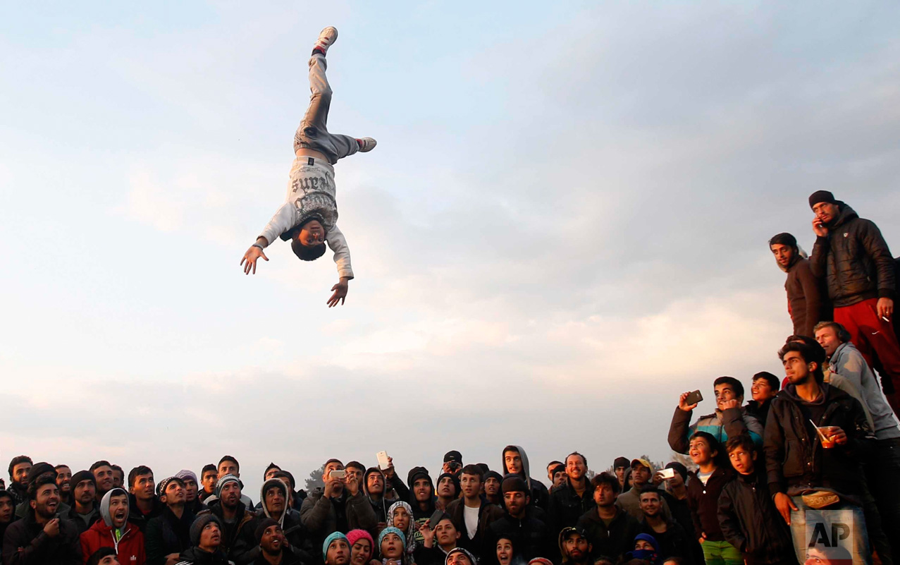 In this Sunday, March 27, 2016 photo, a young migrant is thrown into the air during a party in the northern Greek border station of Idomeni, Greece. A split appears to have developed among migrants at the Idomeni border encampment. Several hundred Iraqis and Syrians are standing between the protesters and the police, in effect thwarting the protesters' efforts to march towards the fence separating Greece from Macedonia. (AP Photo/Darko Vojinovic)