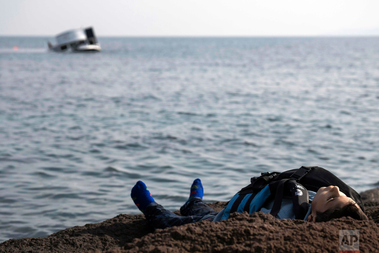 The dead body of a migrant boy lies on the beach near the Aegean town of Ayvacik, Canakkale, Turkey, on Jan. 30, 2016. A boat carrying migrants to Greece hit rocks off the Turkish coast and capsized, killing at least 33 people, including five children, officials and news reports said. (AP Photo/Halit Onur Sandal)