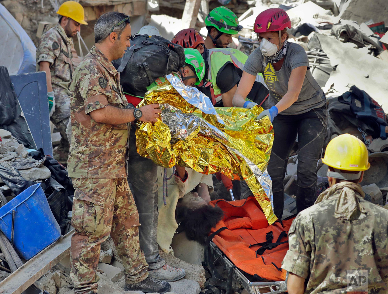 In this Wednesday, Aug. 24, 2016 photo, the body of a victim is pulled out of the rubble following an earthquake in Amatrice Italy. The magnitude 6 quake struck at 3:36 a.m. (0136 GMT) and was felt across a broad swath of central Italy, including Rome where residents of the capital felt a long swaying followed by aftershocks. (AP Photo/Alessandra Tarantino)