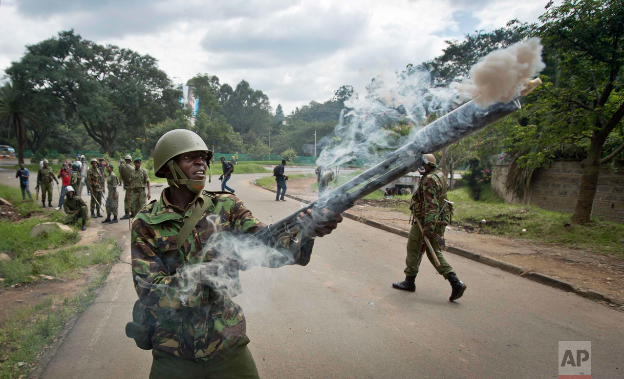 In this Monday, May 9, 2016 photo, a riot policeman fires tear gas towards opposition supporters during a protest in downtown Nairobi, Kenya. Kenyan police have tear-gassed opposition supporters after some pelted police with rocks during a protest demanding the disbandment of the electoral authority over alleged bias and corruption. (AP Photo/Ben Curtis)