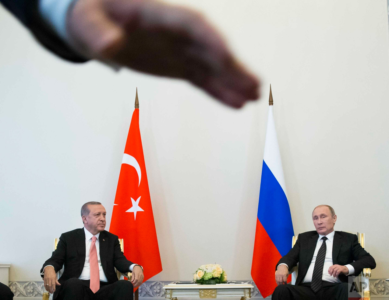 In this Tuesday, Aug. 9, 2016 photo, Russian President Vladimir Putin, right, and Turkish President Recep Tayyip Erdogan talk during their meeting, as a security member tries to stop photographers taking pictures, in the Konstantin palace outside St. Petersburg, Russia. (AP Photo/Alexander Zemlianichenko)